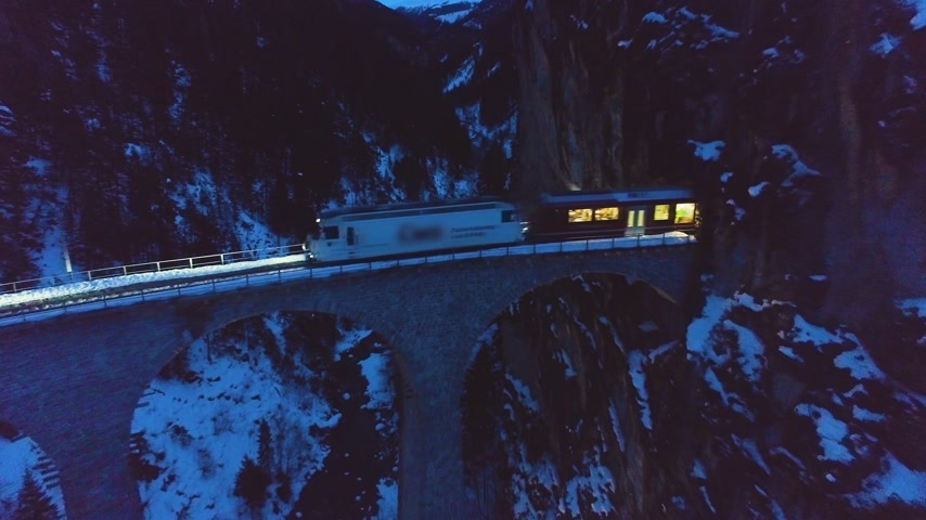 upward : Landwasser Viaduct with Railway and Train at Winter Evening. Mountains, Forest and River. Aerial View. Swiss Old Bridge and Nature. Drone Flies Backwards and Upwards