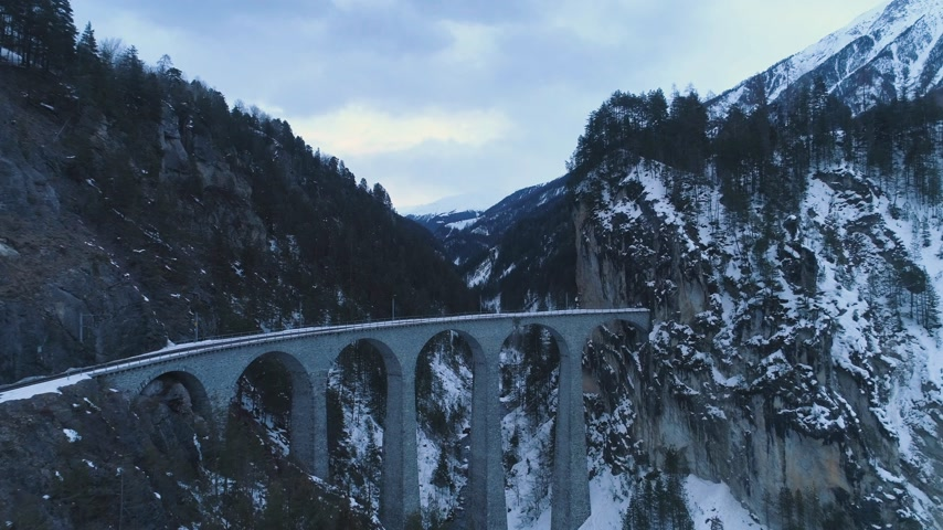tilt down : Landwasser Viaduct with Railway at Winter Day. Mountain Gorge and River. Aerial View. Swiss Alps, Switzerland. Drone Flies Forward, Upwards, Camera Tilts Down