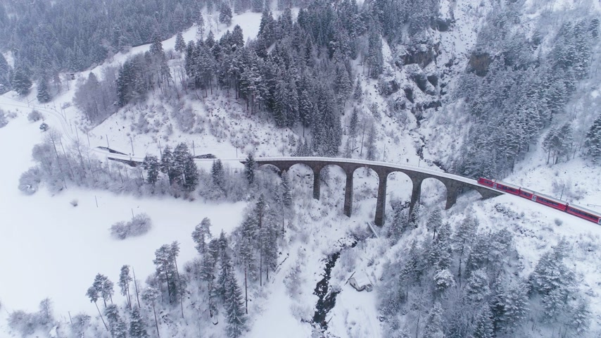 downwards : Viaduct and Train at Winter Day in Swiss Alps. Snowing. Switzerland. Aerial View. Drone Flies Forward and Downward