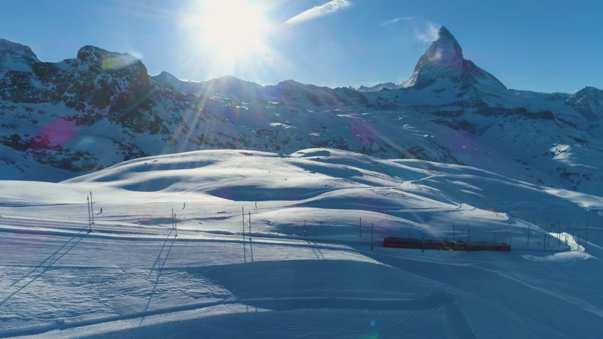 oldalt : Matterhorn Mountain and Gornergrat Train in Sunny Winter Day. Swiss Alps. Switzerland. Aerial View. Drone Flies Sideways, Camera Tilts Up