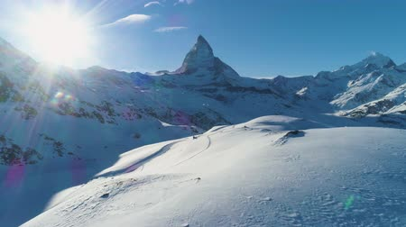 downwards : Blue Matterhorn Mountain in Sunny Winter Day. Swiss Alps. Switzerland. Aerial View. Drone Flies Forward at Low Level