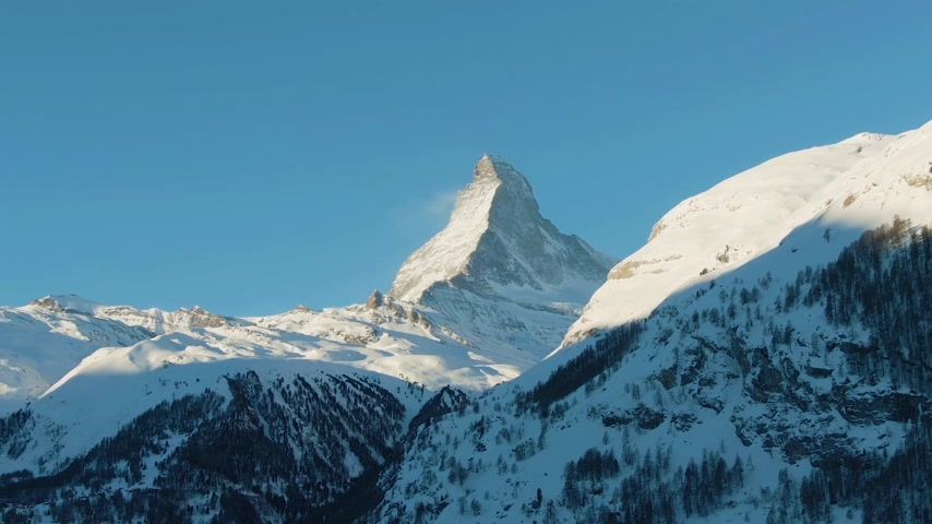 oldalt : Matterhorn Mountain at Sunny Winter Morning. Switzerland. Aerial View. Medium Shot. Drone Flies Sideways