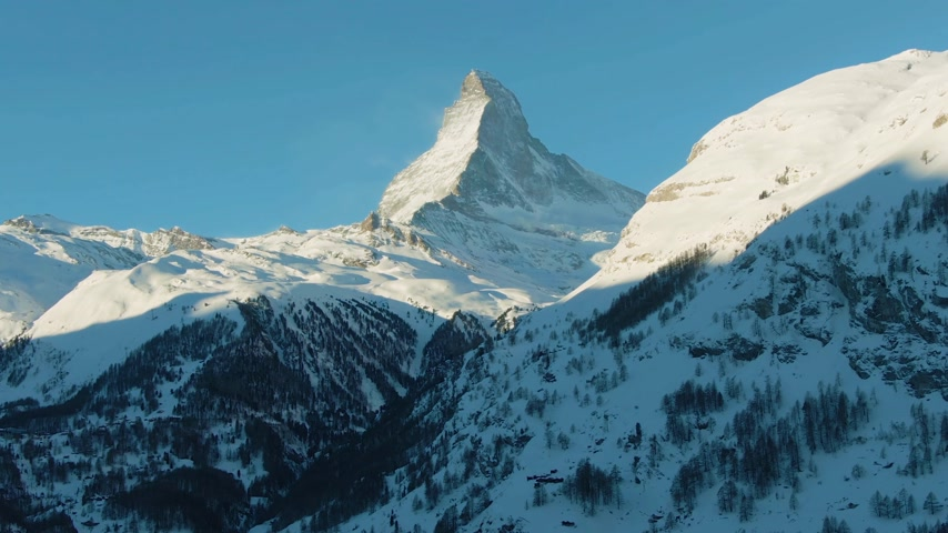upward : Matterhorn Mountain in Winter Day. Switzerland in Snow. Aerial View. Medium Shot. Drone Flies Sideways, Camera Tilts Up