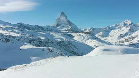 backwards : Matterhorn Mountain and Standing Hiker in Winter Day. Swiss Alps, Switzerland. Low Level Flight Over Man. Aerial View. Drone Flies Backwards