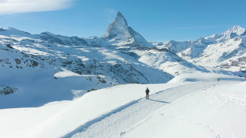 valais : Blue Matterhorn Mountain and Standing Hiker in Winter Day. Swiss Alps, Switzerland. Low Level Flight Over Man. Aerial View. Drone Flies Forward