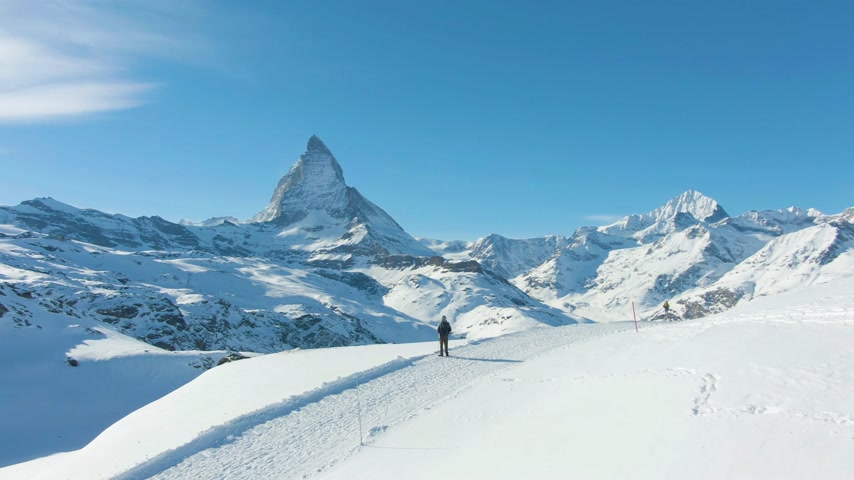valais : Blue Matterhorn Mountain in Winter Day and Hiker Man. Swiss Alps, Switzerland. Aerial View. Drone is Orbiting Stock Footage