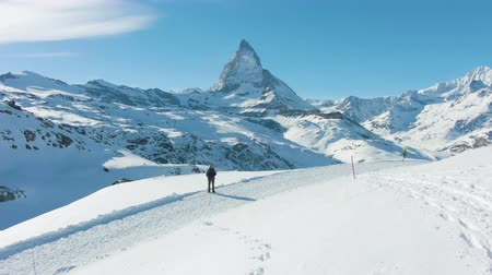 valais : Matterhorn Mountain in Winter Day and Hiker Man. Swiss Alps, Switzerland. Aerial View. Drone is Orbiting Stock Footage