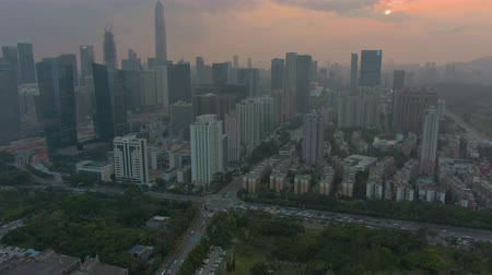 downwards : Shenzhen Urban Cityscape at Sunset. Skyscrapers of Futian District. China. Aerial View. Drone Flies Downwards, Camera Tilts Up. Establishing Shot