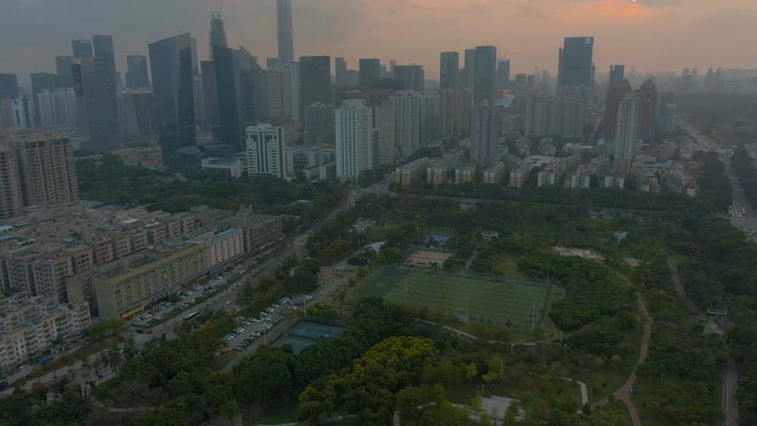 Шэньчжэнь : Shenzhen City at Sunset. Skyscrapers of Futian District. China. Aerial View. Reveal Shot. Drone Flies Forward, Camera Tilts Up