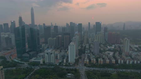 reojo : Cityscape of Shenzhen City at Sunset. Futian District. China. Aerial View. Drone Flies Sideways, Camera Tilts Up Archivo de Video
