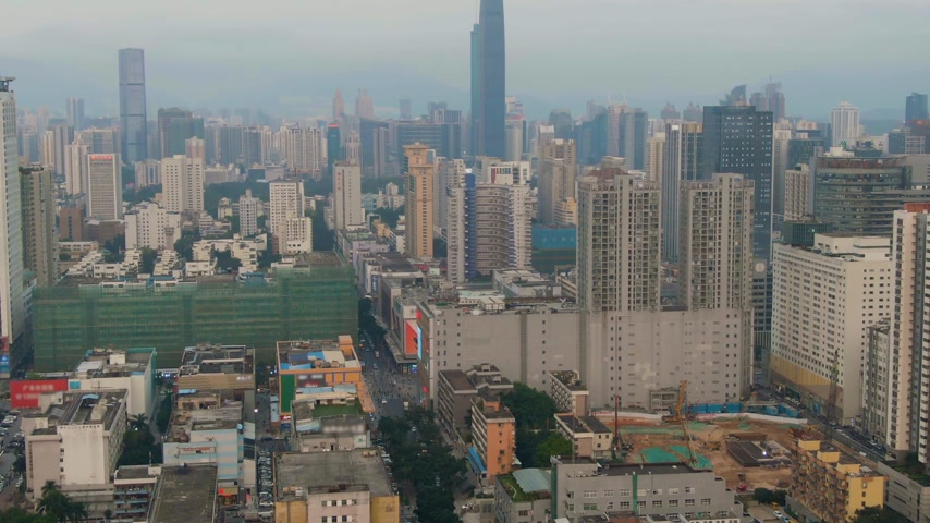 légi felvétel : Shenzhen City. Luohu and Futian District Urban Skyline. China. Aerial View. Medium Reveal Shot. Drone Flies Forward, Camera Tilts Up