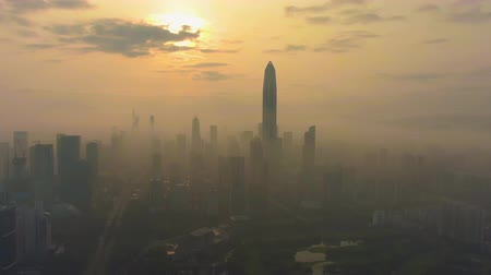establishing shot : Shenzhen Urban Skyline in Fog in the Morning. Futian District. China. Aerial View. Drone is Orbiting