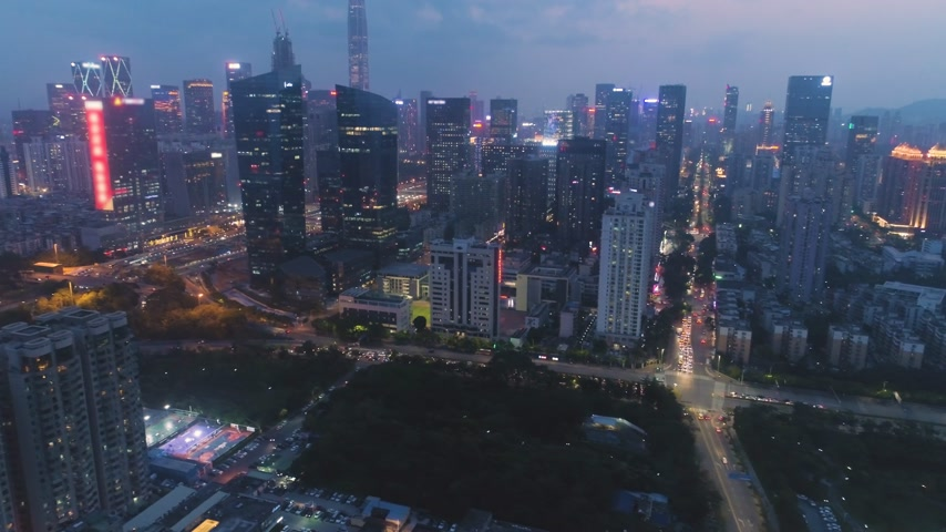 Шэньчжэнь : Shenzhen Skyline at Night. Futian District. Aerial View. China. Drone Flies Sideways and Upwards, Camera Tilts Up