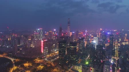 crepúsculo : Shenzhen City Center at Night. Futian District. China. Aerial View. Drone Flies Sideways and Upwards, Tilt Down