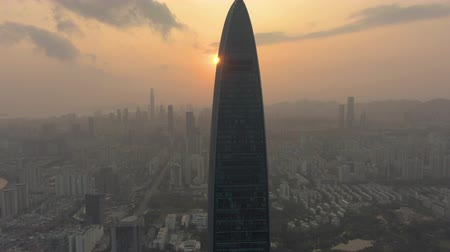 Шэньчжэнь : SHENZHEN, CHINA - MARCH 28, 2019: Kingkey Finance Tower and Urban Skyline at Sunset. Aerial View. Drone is Orbiting Стоковые видеозаписи