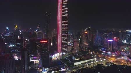 tilt : SHENZHEN, CHINA - MARCH 28, 2019: KK100 Skyscraper and Cityscape at Night. Aerial View. Drone Flies Downwards, Tilt Up Stock Footage