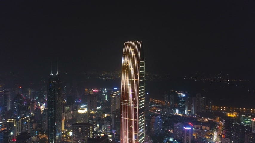 március : SHENZHEN, CHINA - MARCH 28, 2019: KK100 Skyscraper and Urban Skyline at Night. Aerial View. Drone is Orbiting