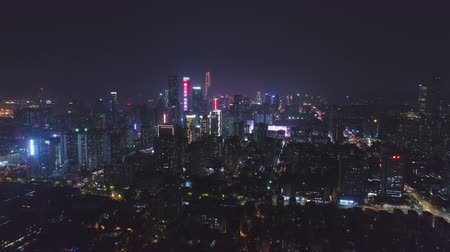 dévoiler : Illuminated Shenzhen Urban City at Night. Futian District. China. Aerial View. Drone Flies Backwards and Upwards