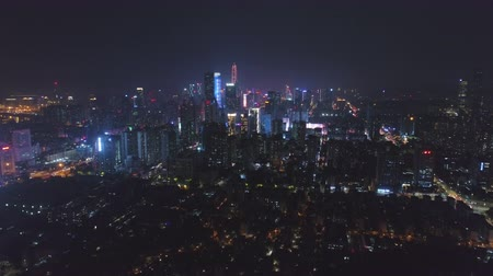 establishing shot : Illuminated Shenzhen Cityscape at Night. Futian District. China. Aerial View. Drone Flies Forward, Tilt Up. Reveal Shot