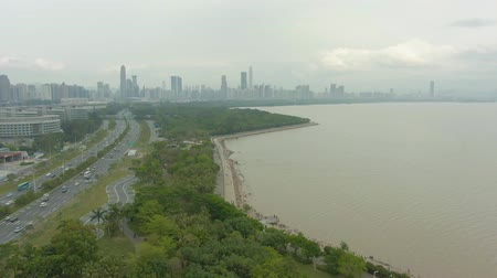 Шэньчжэнь : Shenzhen Cityscape at Day. Futian District Urban Skyline and Bay Park. China. Aerial Shot. Drone Flies Backwards and Upwards Стоковые видеозаписи