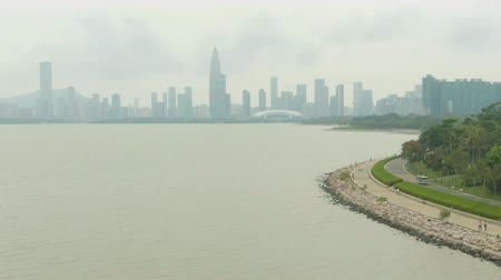 para a frente : Shenzhen City at Day. Nanshan District and Bay Park. China. Aerial Shot. Drone Flies Forward, Medium Shot