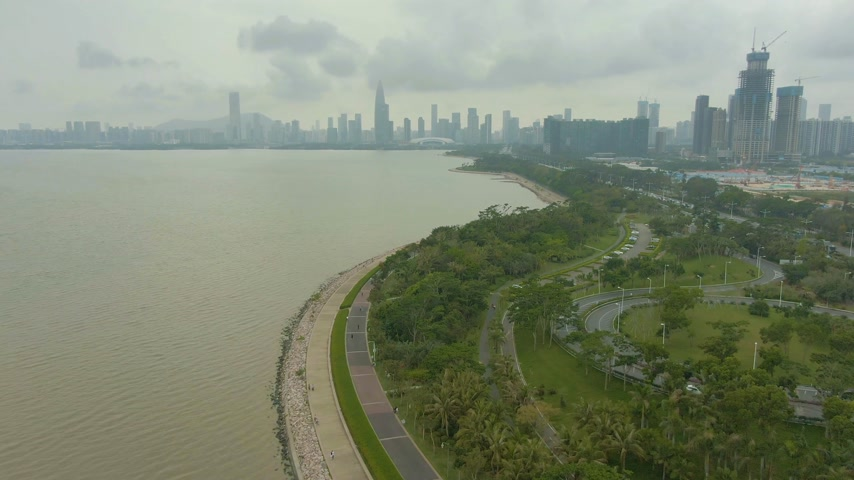 emelkedő : Shenzhen City at Day. Nanshan District Urban Skyline and Bay Park. China. Aerial Reveal Shot. Drone Flies Forward, Tilt Up