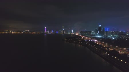 штаб квартира : SHENZHEN, CHINA - MARCH 29, 2019: Nanshan District and Shenzhen Bay at Night. Aerial View. Guangdong. Drone Flies Backwards and Upwards