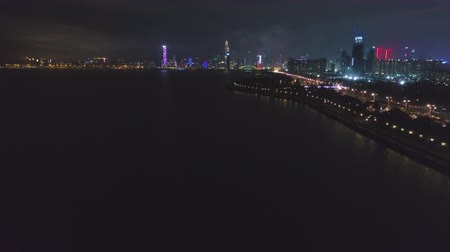 Шэньчжэнь : SHENZHEN, CHINA - MARCH 29, 2019: Nanshan District and Shenzhen Bay at Night. Aerial Reveal View. Drone Flies Forward, Tilt Up. Guangdong