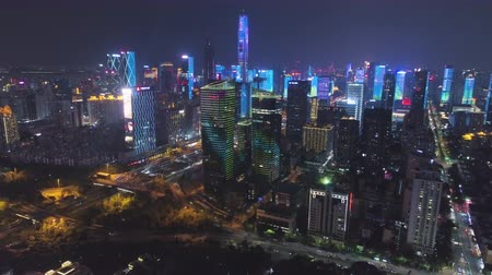 Шэньчжэнь : SHENZHEN, CHINA - MARCH 30, 2019: Urban Skyline and Light Show. Futian District. Aerial View. Reveal Shot. Drone Flies Forward, Tilt Up