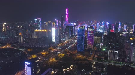 Шэньчжэнь : SHENZHEN, CHINA - MARCH 30, 2019: Urban Cityscape and Light Show. Futian District. Aerial View. Reveal Shot. Drone Flies Sideways and Upwards, Tilt Up Стоковые видеозаписи