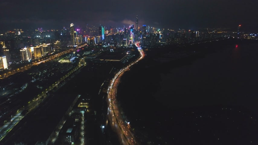 Шэньчжэнь : Shenzhen City at Night. Futian District Urban Skyline and Shenzhen Bay. Guangdong, China. Aerial View. Drone Flies Forward, Tilt Up, Reveal Shot