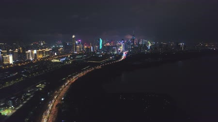 upward : Shenzhen at Night. Futian District Urban Skyline and Shenzhen Bay. Guangdong, China. Aerial View. Drone Flies Sideways, Tilt Up
