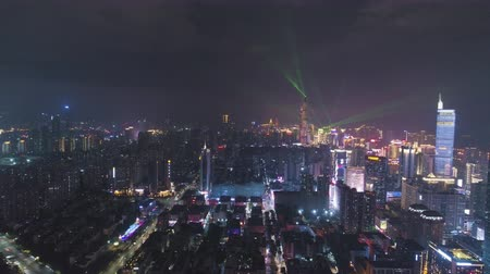 downwards : SHENZHEN, CHINA - MARCH 30, 2019: Illuminated Urban Skyline at Night During Light Show. Futian and Luohu District. Guangdong. Aerial View. Drone Flies Forward and Downwards Stock Footage