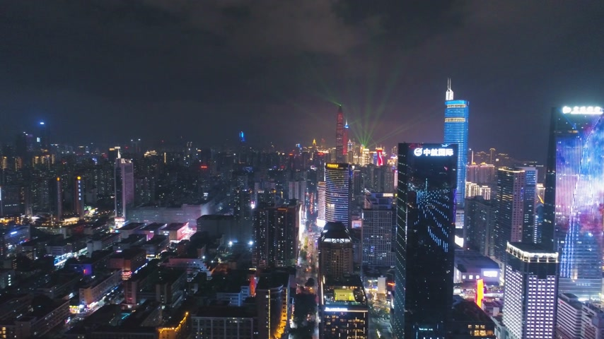 oldalt : SHENZHEN, CHINA - MARCH 30, 2019: Illuminated City at Night During Light Show. Futian and Luohu District. Guangdong. Aerial View. Drone Flies Sideways and Upwards Stock mozgókép