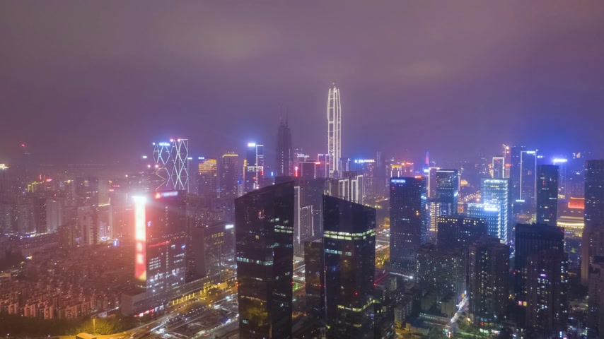 backwards : Shenzhen Urban Cityscape at Night. Urban Futian District. Guangdong, China. Aerial Time Lapse, Hyper Lapse. Drone Flies Backwards and Upwards Stock Footage