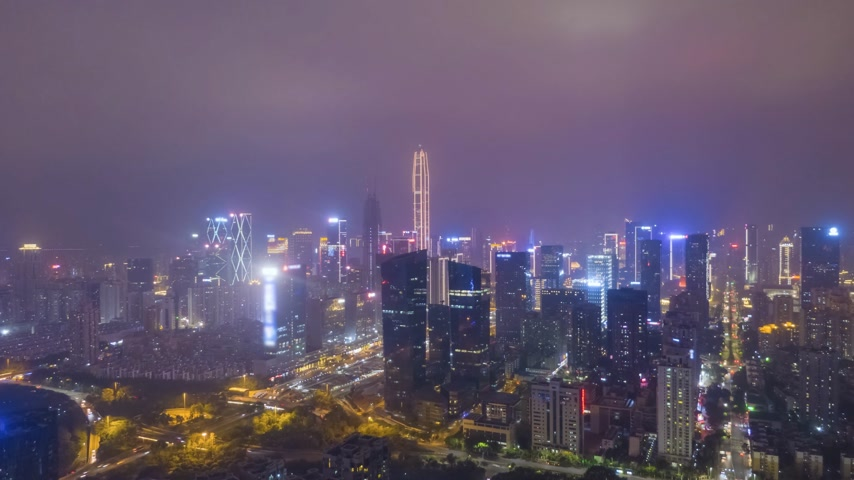 oldalt : Shenzhen City at Night. Urban Futian District. Guangdong, China. Aerial Time Lapse, Hyper Lapse. Drone Flies Sideways and Upwards Stock mozgókép
