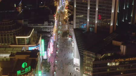 nanjing road : People at Nanjing Road at Night. Pedestrian Street in Huangpu District. Shanghai City, China. Aerial View. Drone Flies Backwards, Tilt Up. Reveal Shot.