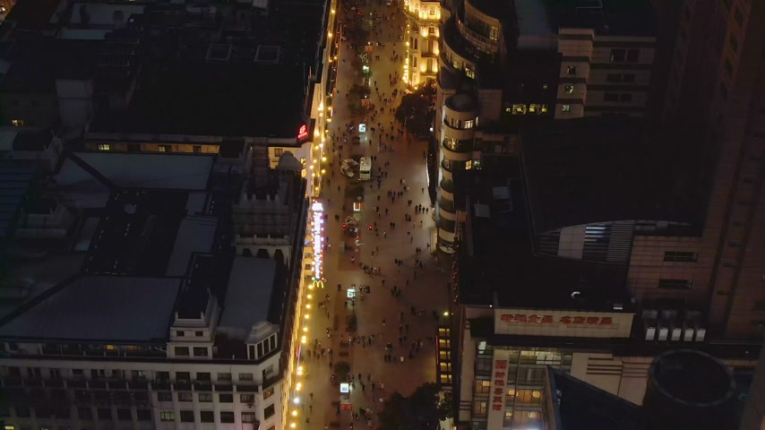 nanjing road : People at Nanjing Road at Night. Pedestrian Street in Huangpu District. Shanghai City, China. Aerial View. Drone Flies Backwards.