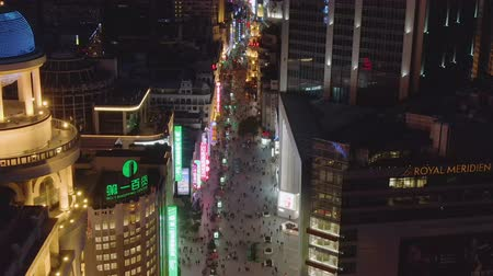 downwards : People at Nanjing Road at Night. Pedestrian Street in Huangpu District. Shanghai City, China. Aerial View. Drone Flies Downwards, Camera Tilts Up, Reveal Shot.