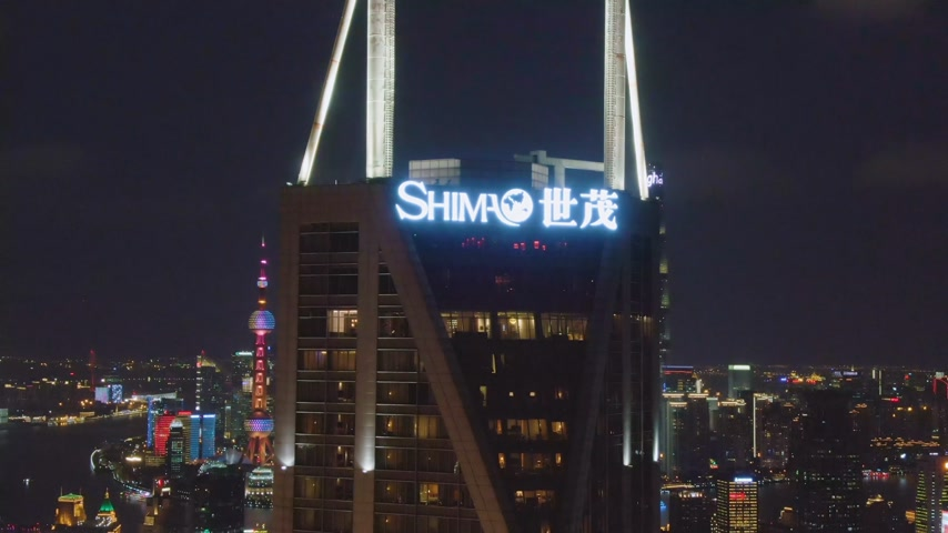 upward : Shimao International Plaza and Lujiazui Skyline at Night. Shanghai City, China. Aerial View. Drone Flies Upwards, Tilt Down.