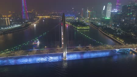 the suspension bridge : Liede Bridge on Pearl River and Guangzhou Cityscape at Night. China. Aerial View. Drone is Orbiting Stock Footage