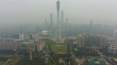 tilt : GUANGZHOU, CHINA - MARCH 25, 2018: Canton Tower and City Skyline in Smog in the Morning. Aerial View. Drone Flies Backwards, Tilt Up. Reveal Shot. Stock Footage