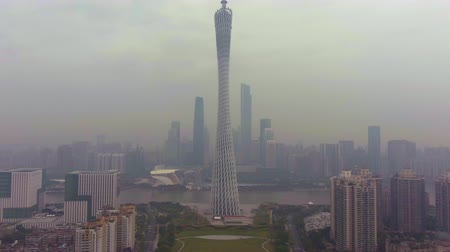 emelkedő : GUANGZHOU, CHINA - MARCH 25, 2018: Canton Tower and City Skyline in Smog in the Morning. Aerial View. Drone Flies Backwards and Upwards. Reveal Shot.