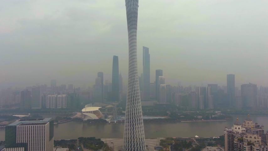 downwards : GUANGZHOU, CHINA - MARCH 25, 2018: Canton Tower and City Skyline in Smog in the Morning. Aerial View. Drone Flies Downwards, Tilt Up.