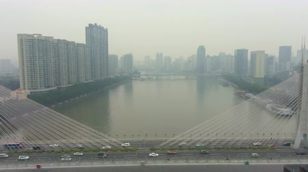 backwards : Bridge in Guangzhou in Smog, Car Traffic and Cityscape. Guangdong, China. Aerial View. Drone Flies Backwards
