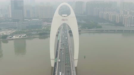 the suspension bridge : Liede Bridge on Pearl River. Guangzhou City in Smog, China. Aerial View. Drone is Orbiting Counterclockwise