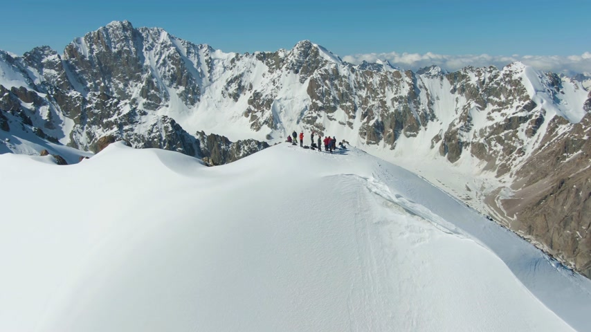 kilátás : People on Top of Snow-Capped Mountain in Sunny Day. Aerial View. Drone is Orbiting Counterclockwise Stock mozgókép