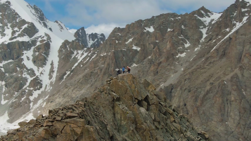tampado : Four Climbers on Peak of Rock. Snow-Capped Mountains. Aerial View. Drone is Orbiting