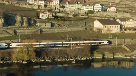 geneva : Passenger Train Goes Along Lake Geneva Shore. Reflection in Water. Terraced Vineyards of Lavaux and Village. Switzerland. Aerial Shot. Drone Flies Sideways Stock Footage