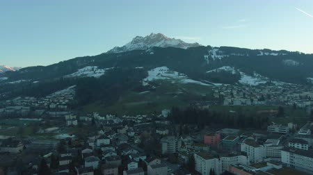 backwards : Kriens City and Mountain Pilatus at Sunset in Winter. Swiss Alps, Switzerland. Aerial View. Drone Flies Backwards Stock Footage